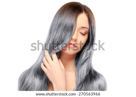 Fresh and beautiful. Portrait of beautiful young woman with closed eyes and holding hand on her long gray hair while standing against white background - stock photo