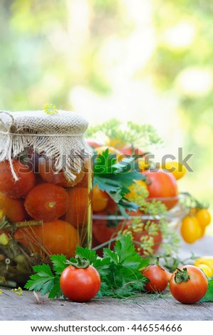 Fresh and canned tomatoes on old wooden table