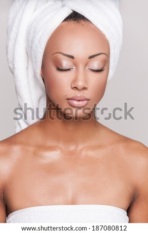 Fresh and clean. Beautiful young Afro-American shirtless woman keeping eyes closed while standing on gray background - stock photo