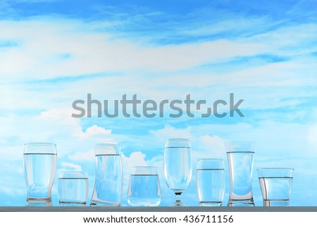 Fresh and clean drinking water in assortment of glasses on sky background - stock photo
