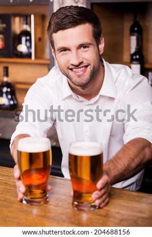 Fresh and cold beer for you! Handsome young male bartender in white shirt holding glasses with beer and smiling while standing at the bar counter