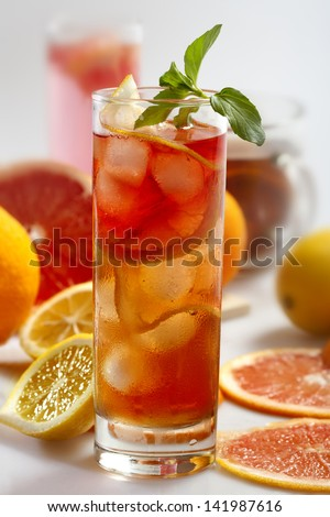Fresh and cold ice tea with sliced grapefruit, lemon and mint