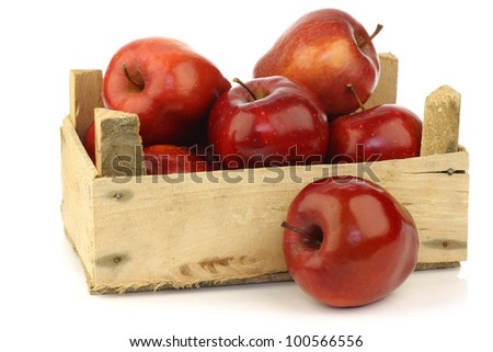 Fresh and delicious red Ambrosia apples in a wooden crate  on a white background - stock photo