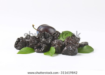 fresh and dried plums on white background - stock photo