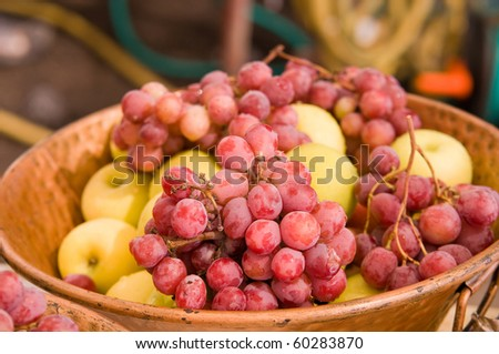 Fresh and juicy grapes in a bowl with red apples in the background .