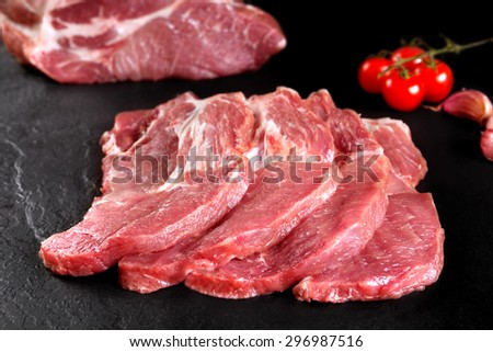 Fresh and raw meat. Pork tenderloin, loin  medallions Steaks in a row ready to cook. Background black blackboard.