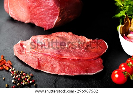 Fresh and raw meat. Steaks in a row ready to cook. Black slate background. Butchers' meat. - stock photo