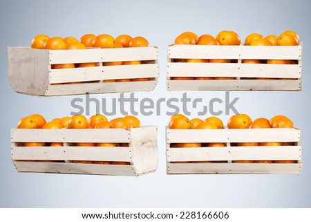 Fresh and Ripe Orange Fruits in a Wooden Box isolated on Blue Studio Background - stock photo