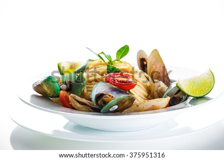 Fresh and spicy seafood pasta in white plate on white background - stock photo