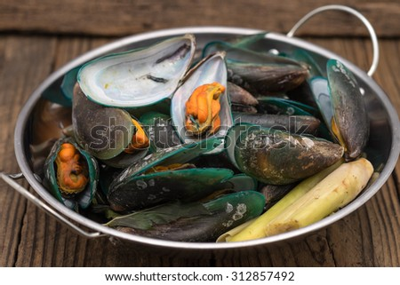 Fresh and steamed green mussels with herb in silver pot on wood table for seafood cuisine background  - stock photo