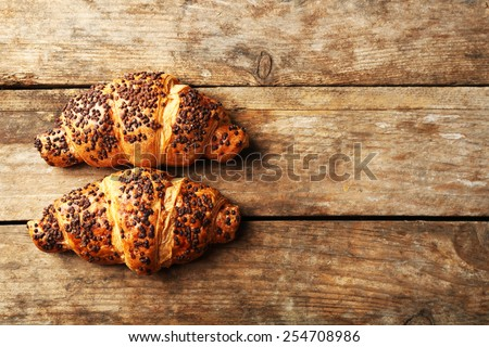 Fresh and tasty croissants with chocolate on wooden background - stock photo