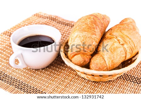 Fresh and tasty French croissants in a basket and cup of coffee served isolated on white background