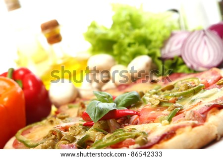 Fresh and tasty pizza on kitchen table - stock photo