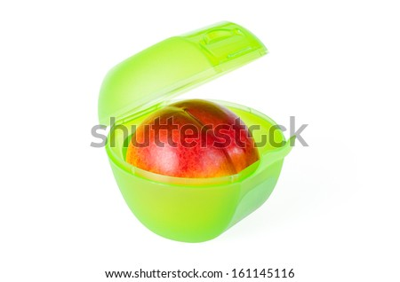 Fresh and tasty red peach in a green school lunch box - stock photo