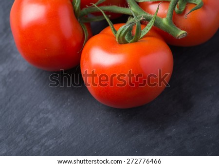 Fresh and tasty red tomatoes on a black stone serving board - stock photo