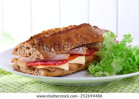 Fresh and tasty sandwich with ham and lettuce on plate on wooden background - stock photo