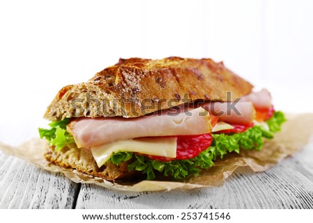 Fresh and tasty sandwich with ham and vegetables on table on light background - stock photo