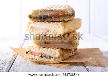 Fresh and tasty sandwiches on paper on wooden background - stock photo