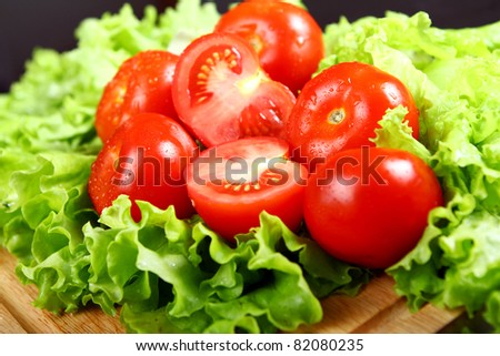 Fresh and wet tomatoes lying on the salad leaves - stock photo