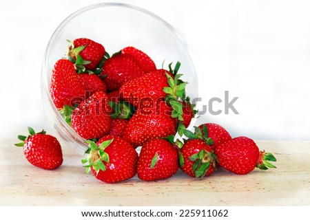 fresh appetizing red strawberries scattered from in glass bowl - stock photo