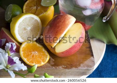 fresh apple and cirtus on cutting board - stock photo