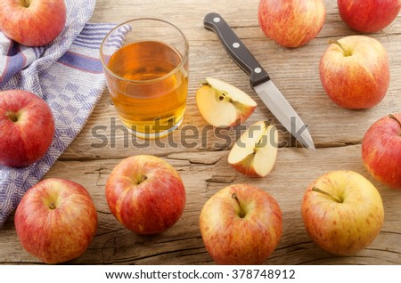 fresh apple juice and apples on rustic wooden table - stock photo