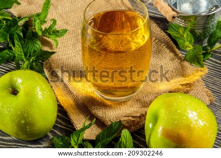 Fresh apple juice and ripe fruits arranged on a wooden table - stock photo