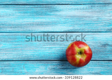 Fresh apple on a blue wooden table - stock photo