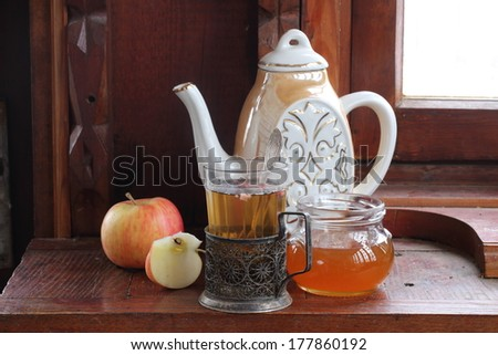 Fresh apple tea in a glass glass in a copper coaster submitted with sweet fragrant honey and juicy red ripe apples - stock photo