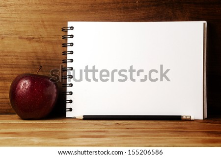 Fresh apple with drops of water,paper and pencil on wood table. - stock photo