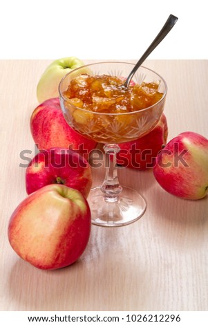 Fresh apples and jam of them in a vase on white background