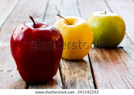 Fresh apples on rustic wooden background. Selective focus.