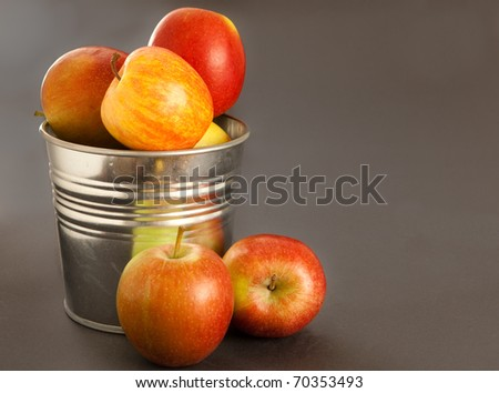 Fresh apples overflowing from a rustic metal container