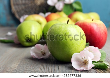 Fresh apples with apple blossom on wooden table - stock photo