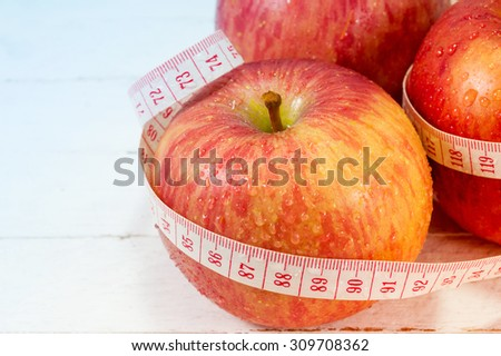 Fresh apples with measure tape on white wood background, object for diet concept.  - stock photo