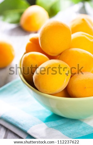 fresh apricots with leafs on wooden table