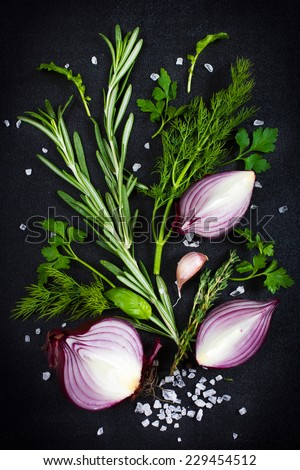 Fresh aromatic herbs with red onion, garlic and sea salt on a black background , top view - stock photo