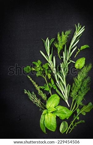 Fresh aromatic herbs with water drops on a black background , top view - stock photo