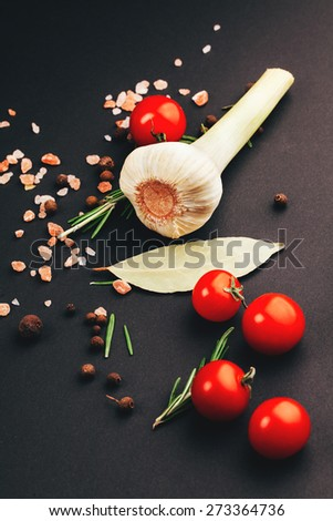 Fresh aromatic tomatoes, herbs and spices on a black background - stock photo