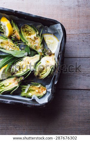 Fresh artichokes with parsley and young beans in a baking pan. Top view. - stock photo