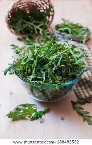 Fresh arugula in a glass plate on the wood  table