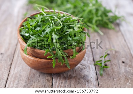 Fresh arugula in the wooden bowl, selective focus