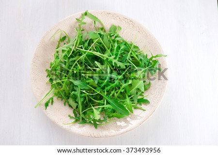 fresh arugula leaves in the plate on the white background - stock photo