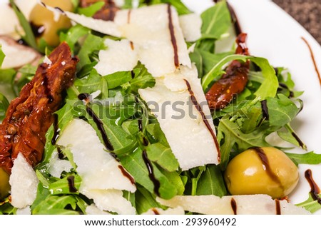 Fresh arugula with grated parmesan covered with balsamic vinegar. Macro. Photo can be used as a whole background. - stock photo