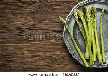 Fresh asparagus on a plate and wooden background.
