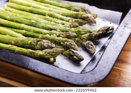 Fresh asparagus spears with salt, pepper and oil ready to be grilled or roasted - stock photo