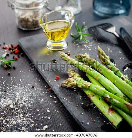 Fresh asparagus with olive oil and seasonings and ingredients for cooking on dark background. Shallow focus.