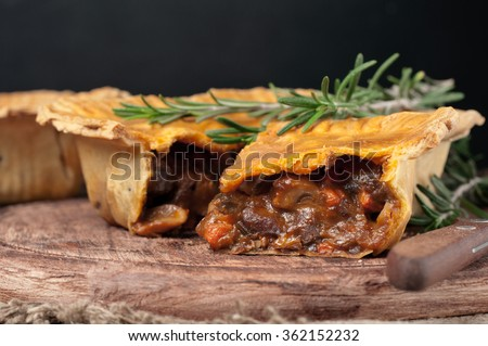 Fresh australian meat pie on the wooden table closeup with copy space, rustic style - stock photo