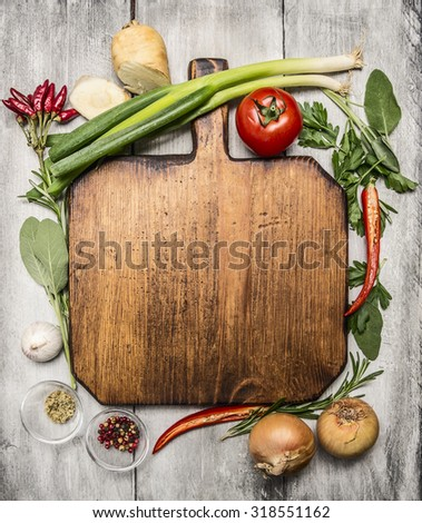 fresh autumn  and vegetables seasonings and hearbs around a wooden cutting board on bright, rustic wood background top view