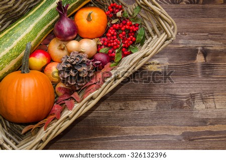 fresh autumn vegetables in a basket (pumpkin, apple, cone, onion) - stock photo